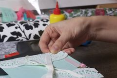 The girl is engaged in making greeting cards at home. Using paper, lace, braid and other materials. The girl is engaged in making greeting cards at home. Using Royalty Free Stock Image