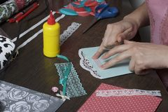 The girl is engaged in making greeting cards at home. Using paper, lace, braid and other materials. The girl is engaged in making greeting cards at home. Using Stock Images