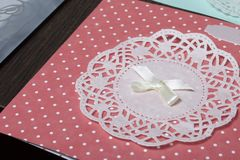 The girl is engaged in making greeting cards at home. Using paper, lace, braid and other materials. The girl is engaged in making greeting cards at home. Using Stock Image