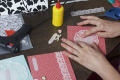 The girl is engaged in making greeting cards at home. Using paper, lace, braid and other materials. The girl is engaged in making greeting cards at home. Using Stock Photography