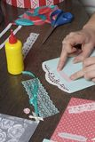 The girl is engaged in making greeting cards at home. Using paper, lace, braid and other materials. The girl is engaged in making greeting cards at home. Using Royalty Free Stock Images