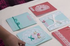 The girl is engaged in making greeting cards at home. Using paper, lace, braid and other materials. The girl is engaged in making greeting cards at home. Using Royalty Free Stock Photos