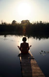Girl is engaged in meditation on the small bridge Stock Photo
