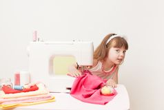 The girl is engaged in needlework using sewing machine Stock Photography