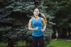 The girl is engaged in sports running in the park. Training on the street in the summer morning. Concept sport healthy lifestyle stock photos