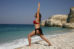 The girl is engaged in yoga. On seacoast in a bathing suit (a pose of the hero Stock Photo