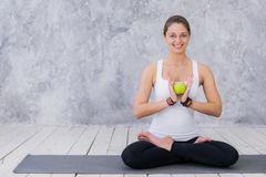 Girl is engaged in yoga on a white background, concept of healthy lifestyle, healthy eating and sport, apples Stock Image