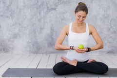 Girl is engaged in yoga on a white background, concept of healthy lifestyle, healthy eating and sport, apples Royalty Free Stock Photo