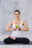 Girl is engaged in yoga on a white background, concept of healthy lifestyle, healthy eating and sport, apples Royalty Free Stock Photography
