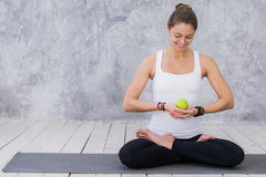 Girl is engaged in yoga on a white background, concept of healthy lifestyle, healthy eating and sport, apples Royalty Free Stock Image