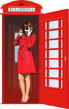 Girl in an English phone booth Royalty Free Stock Photography