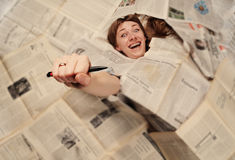 Girl engulfed with newspapers. And holding pen in the hand Stock Images