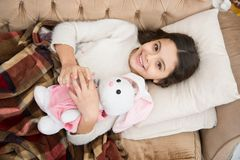 Girl enjoy evening time with favorite toy. Kid lay bed and hug bunny toy couch pillow blanket background top view. Girl royalty free stock image