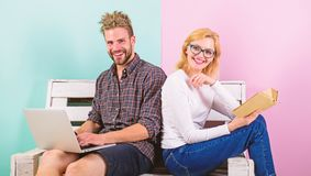 Girl enjoy her life while husband freelancer works with laptop. Woman smiling face reading book near man working royalty free stock photos