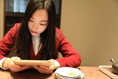 Girl  Enjoy leisure time,read book and drink tea. A Chinese girl in red dress  is performing tea art. China has history of tea culture for more than one thousand Stock Photos