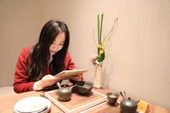 Girl  Enjoy leisure time,read book and drink tea. A Chinese girl in red dress  is performing tea art. China has history of tea culture for more than one thousand Royalty Free Stock Images