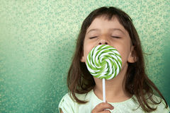 Girl enjoy licking a lollipop. Royalty Free Stock Images