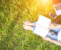 Girl enjoy reading book and play laptop on the grass filed of park Royalty Free Stock Image