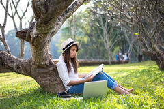Girl enjoy reading a book under the tree, laying on grass of park Royalty Free Stock Photography