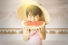Girl enjoy a watermelon at coast Royalty Free Stock Photography