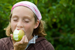 Girl enjoying an apple. Tween girl eating a fresh picked apple Stock Images