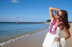 Girl enjoying beach getaway. Hawaii woman with flower lei garland of pink orchids. Beautiful smiling woman in white dress on beach. Summer luxury vacation in Stock Images
