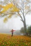 Girl enjoying beautiful autumn forest on foggy morning. Royalty Free Stock Photo