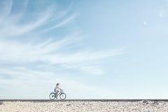 Girl enjoying bike ride under sky Royalty Free Stock Photo