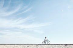 Girl enjoying bike ride under sky Stock Photos