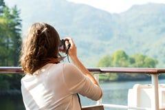 Girl enjoying boat ride, taking photographs Stock Images