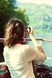 Girl enjoying boat ride, taking photographs. Unrecognizable young female enjoying boat ride, taking photographs, Loch Katrina, Scottish Highlands, UK royalty free stock image