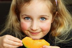 Girl Enjoying Cantaloupe Stock Photos