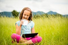 Girl enjoying chocolate and watching tablet Royalty Free Stock Image