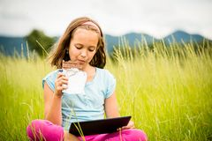 Girl enjoying chocolate and watching tablet Stock Images