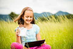 Girl enjoying chocolate and watching tablet Royalty Free Stock Photo