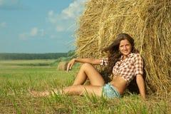 Girl enjoying on fresh straw Stock Photography