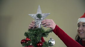 Girl enjoying getting shiny star on Christmas tree in slow motion stock footage