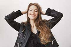 Girl enjoying independence and carefree mood. Relaxed feminine european woman with beautiful long hair closing eyes. Holding hands on head and smiling while Stock Photography
