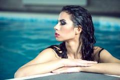 Girl enjoying in indoor pool. Close up portrait of young attractive woman enjoying swimming in indoor pool. Wellness resort interior Stock Image