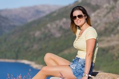 Girl enjoying the lake. Young happy woman sitting on the rock mountain, relaxing and enjoying the lake at Geres, Portuguese National Park royalty free stock photography