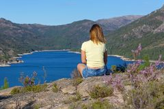 Girl enjoying the lake. Young woman sitting on the rock mountain, relaxing and enjoying the lake at Geres, Portuguese National Park stock image