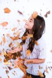 Girl and Leaves in Autumn. Girl enjoying leaves falling on her during Autumn Stock Photography