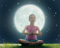 Girl enjoying meditation and yoga. Cute little child girl enjoying meditation and yoga on green grass on moon sky background Stock Photo