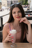 A girl is enjoying a milkshake at a summer cafe. Sunny summer day in the city stock photos