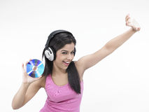 Girl enjoying music. Beautiful young asian girl grooving to the music Royalty Free Stock Images
