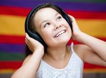 Girl is enjoying music using headphones Royalty Free Stock Photos
