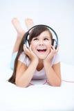 Girl is enjoying music using headphones Stock Image