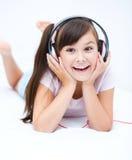 Girl is enjoying music using headphones Royalty Free Stock Photography