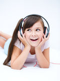 Girl is enjoying music using headphones Stock Images