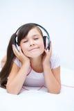 Girl is enjoying music using headphones Stock Photography